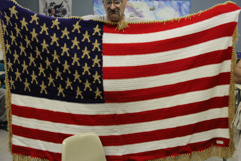 Eric Fowler, a member of the veteran�s club at James Crabtree Correctional Center, holds up a gold star  American flag afghan. Veterans at the prison make the afghans for other veterans and for families who have lost soldiers in combat. Photo by Darryl Golden, The Oklahoman
