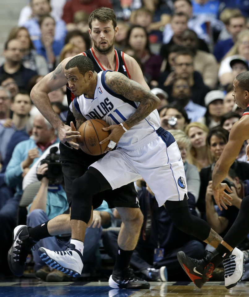 Photo - Portland Trail Blazers center Joel Freeland defends against a drive to the basket by Dallas Mavericks' Monta Ellis (11) during the first half of an NBA basketball game, Saturday, Jan. 18, 2014, in Dallas. (AP Photo/Tony Gutierrez)