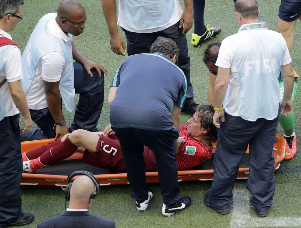 Photo - Portugal's Fabio Coentrao is taken away on a stretcher after being injured during the group G World Cup soccer match between Germany and Portugal at the Arena Fonte Nova in Salvador, Brazil, Monday, June 16, 2014.  (AP Photo/Christophe Ena)