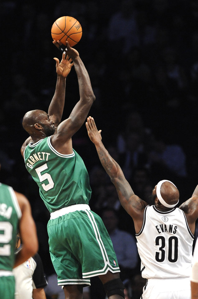 Boston Celtics' Kevin Garnett (5) takes aim over Brooklyn Nets' Reggie Evans (30) in the first half of an NBA basketball game on Thursday, Nov., 15, 2012, at Barclays Center in New York. (AP Photo/Kathy Kmonicek)