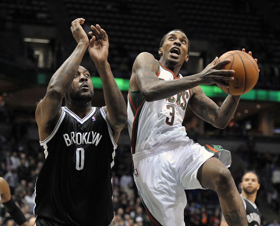 Brooklyn Nets' Andray Blatche (0) defends as the Milwaukee Bucks' Brandon Jennings (3) drives to the basket during the second half of an NBA basketball game Wednesday, Feb. 20, 2013, in Milwaukee. The Nets defeated the Bucks 97-94. (AP Photo/Jim Prisching)