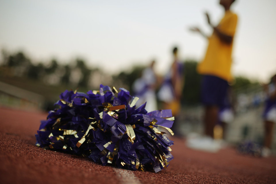 A pom sits on the ground as cheerleaders clap at the Northwest Classen vs. Western Heights high school football game at Taft Stadium Thursday, September 20, 2012. Photo by Doug Hoke, The Oklahoman
