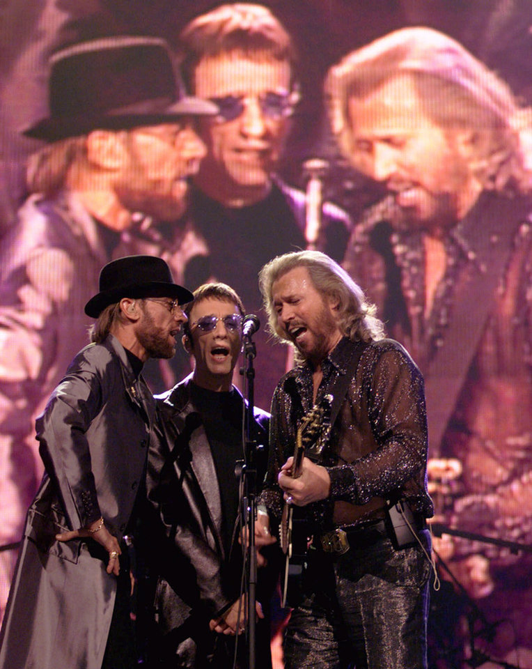 Photo -   FILE - In this Dec. 31, 1999, file photo, The Bee Gees, from left, Maurice, Robin and Barry Gibb, perform in front of their projected images at the