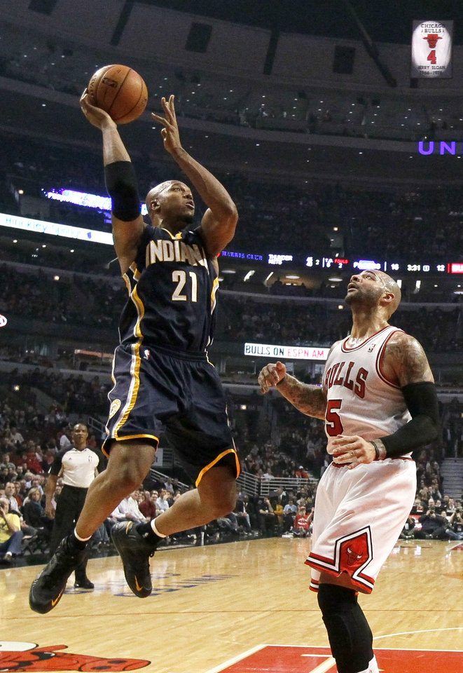 Indiana Pacers forward David West (21) shoots over Chicago Bulls forward Carlos Boozer during the first half of an NBA basketball game Tuesday, Dec. 4, 2012, in Chicago. (AP Photo/Charles Rex Arbogast)