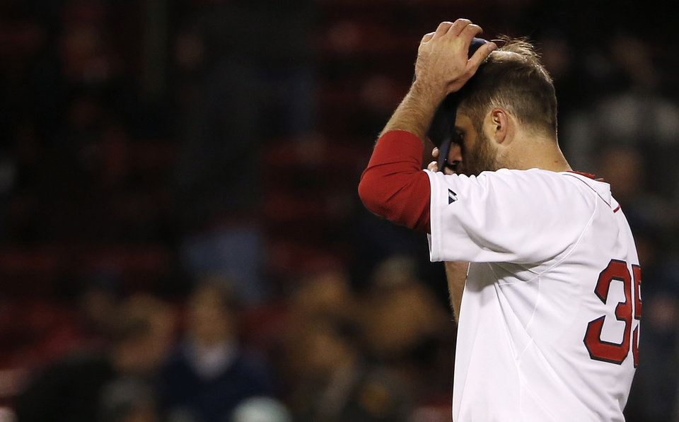 Photo - Boston Red Sox relief pitcher Burke Badenhop adjusts his cap after giving up the go-ahead run during the eleventh inning of a baseball game against the Milwaukee Brewers at Fenway Park in Boston, Saturday, April 5, 2014. (AP Photo/Winslow Townson)