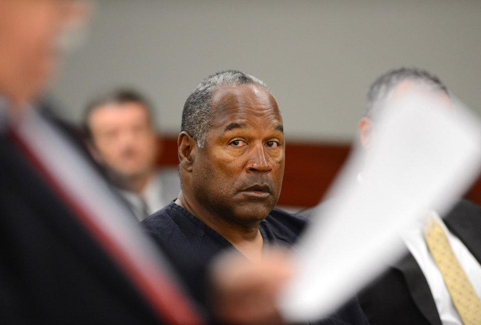 Photo - O.J. Simpson looks over at his lawyer Tom Pitaro during an evidentiary hearing in Clark County District Court on May 17, 2013 in Las Vegas. Simpson, who is currently serving a nine-to-33-year sentence in state prison as a result of his October 2008 conviction for armed robbery and kidnapping charges, is using a writ of habeas corpus to seek a new trial, claiming he had such bad representation that his conviction should be reversed.  (AP Photo/Ethan Miller, Pool)
