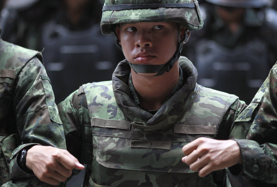 Photo - Thai soldiers link arms as they monitor the protest against the coup outside a shopping complex in Bangkok, Thailand Saturday, May 24, 2014. Thailand's coup leaders said Saturday they will keep former Prime Minister Yingluck Shinawatra, Cabinet members and anti-government protest leaders detained for up to a week to give them