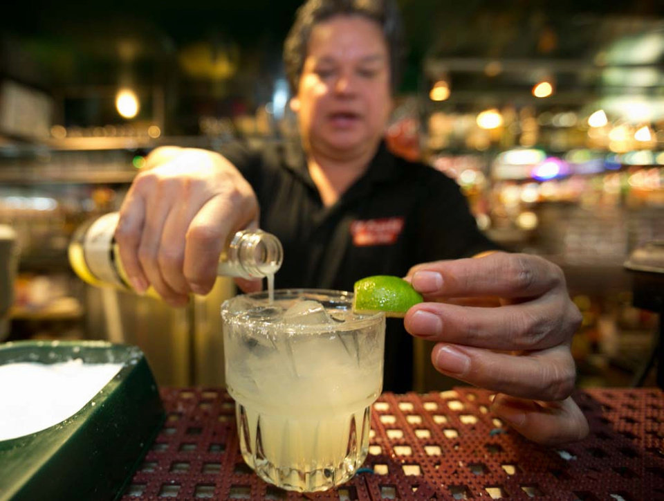 Photo - In this Monday, April 28, 2014 photo, bartender Mario Sanchez crafts a margarita cocktail at the bar of El Coyote, a Mexican restaurant in Los Angeles. Thousands of restaurateurs from coast to coast who have fallen victim to the Great Green Citrus Crisis of 2014. The lime has skyrocketed in price in recent weeks, quadrupling or, in some areas, going even higher. (AP Photo)