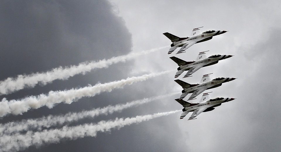 Four jets from the Thunderbirtd flying team fly in close formation Saturday. Base officials estimate more than 100,000 visitors will attend Tinker Air Force Base's annual Star Spangled Salute Air Show and Open House this Saturday and Sunday, June 21 and 22, 2014.  The Air Force Thunderbirds, a military  precision flying team,  thrilled spectators with their close formations and daredevil-type flying Saturday afternoon.  Organizers say the public will have an opportunity to view the largest collection of static displays in  the history of the event.  Hundreds stood in long lines in hot and humid conditions to walk through the E-3 Sentry on Saturday.  Visitors also were able to get close looks at other military aircraft,  including the B-1B Lancer, B-52 Stratofortress, C-17 Globemaster, CV-22 Osprey, E-6B Mercury, KC-135 Stratotanker.  The event continues on Sunday, with aerial acts starting at noon. Photo by Jim Beckel, The Oklahoman
