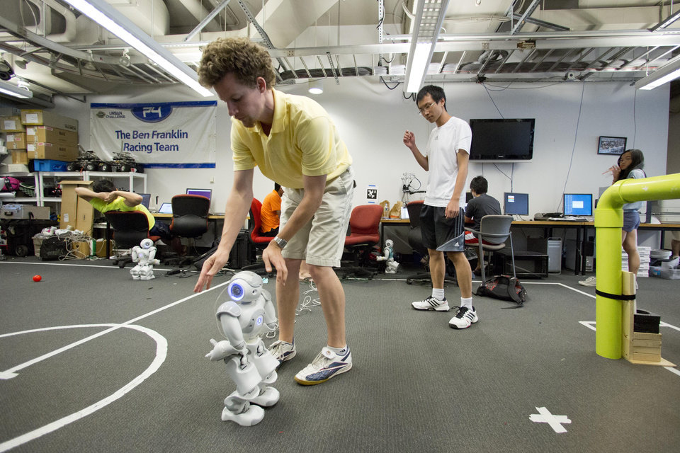 Photo - In this July 7, 2014, photo, Ph.D. candidate Stephen McGill works with a Nao RoboCup entree at the University of Pennsylvania in Philadelphia. The international robot soccer tournament called RoboCup takes place in Brazil right after the World Cup. The ultimate goal of the yearly event is bold: To create a robot team that can defeat the human World Cup winners by 2050.  (AP Photo/Matt Rourke)