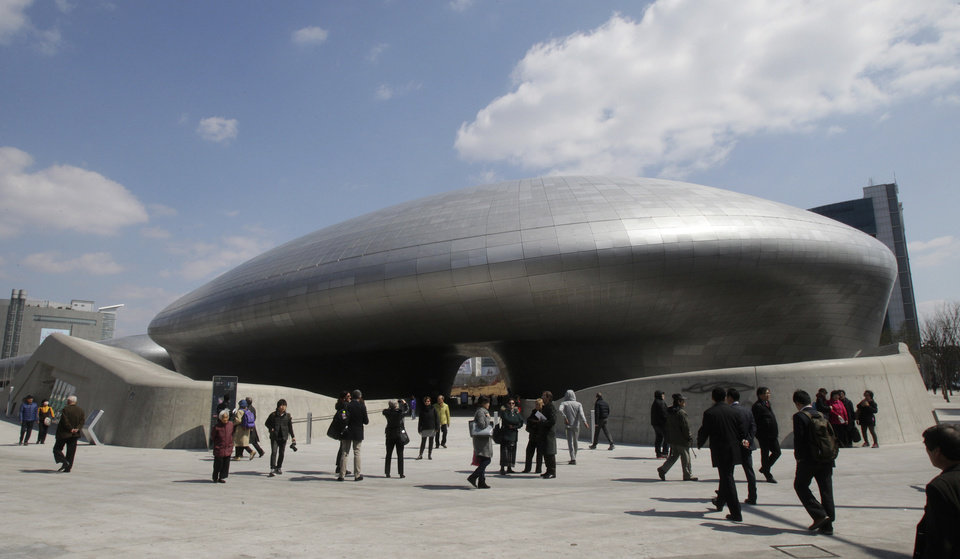 Photo - Visitors are dwarfed by Dongdaemun Design Plaza in Seoul, South Korea, Friday, March 21, 2014. The $450 million building funded by Seoul citizen's tax money finally opened to public on Friday after years of debates about transforming a historic area with an ultra-modern architecture.(AP Photo/Ahn Young-joon)