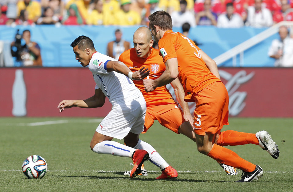 Photo - Chile's Alexis Sanchez, left, is challenged by Netherlands' Stefan de Vrij, right, and Arjen Robben during the group B World Cup soccer match between the Netherlands and Chile at the Itaquerao Stadium in Sao Paulo, Brazil, Monday, June 23, 2014. (AP Photo/Frank Augstein)