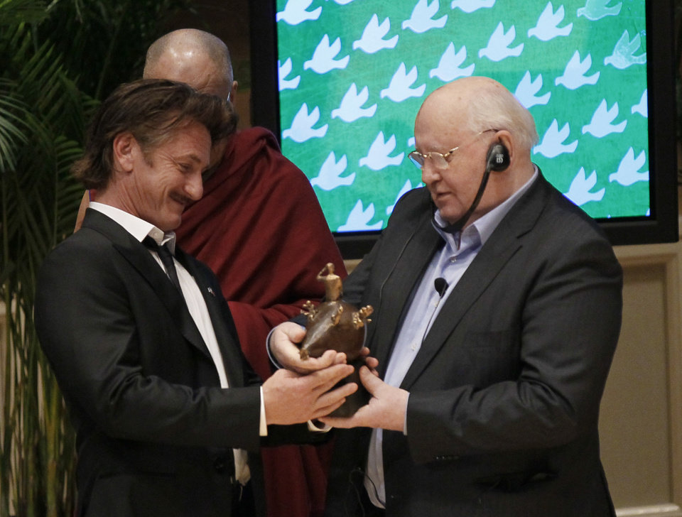 Photo -   Mikhail Gorbachev, former President of the Union of Soviet Socialist Republics, right, presents actor Sean Penn the 2012 Peace Summit Award during the World Summit of Nobel Peace Laureates Wednesday, April 25, 2012, in Chicago. His Holiness the Dalai Lama watches at rear. (AP Photo/Charles Rex Arbogast)