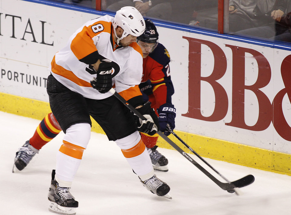 Photo - Philadelphia Flyers defenseman Nicklas Grossmann (8) and Florida Panthers left wing Sean Bergenheim (20) fight for the puck during the second period of an NHL hockey game in Sunrise, Fla., on Tuesday, April 8, 2014. (AP Photo/Terry Renna)
