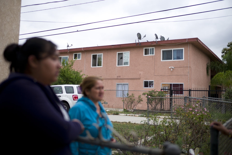 Photo - A group of women from the neighborhood chat near an apartment building where suspect Isidro Garcia lived on Thursday, May 22, 2014, in Bell Gardens, Calif. A woman who disappeared a decade ago as a 15-year-old reunited recently with her mother, who convinced her to go to authorities to report that she had been kidnapped and raped by Garcia who is now her husband and father of her daughter. (AP Photo/Jae C. Hong)