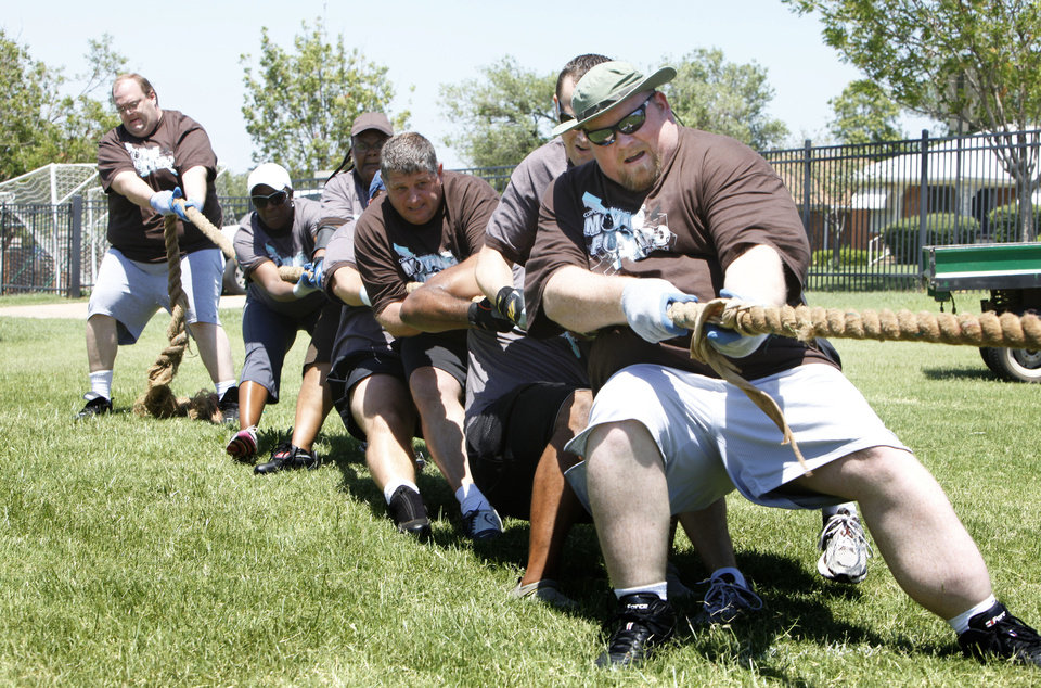 Photo - Jonathon Denton takes the lead position for American Fidelity in the tug-o-war event during the Corporate Challenge at Bishop McGuiness High School.Photos by PAUL HELLSTERN, the oklahoman