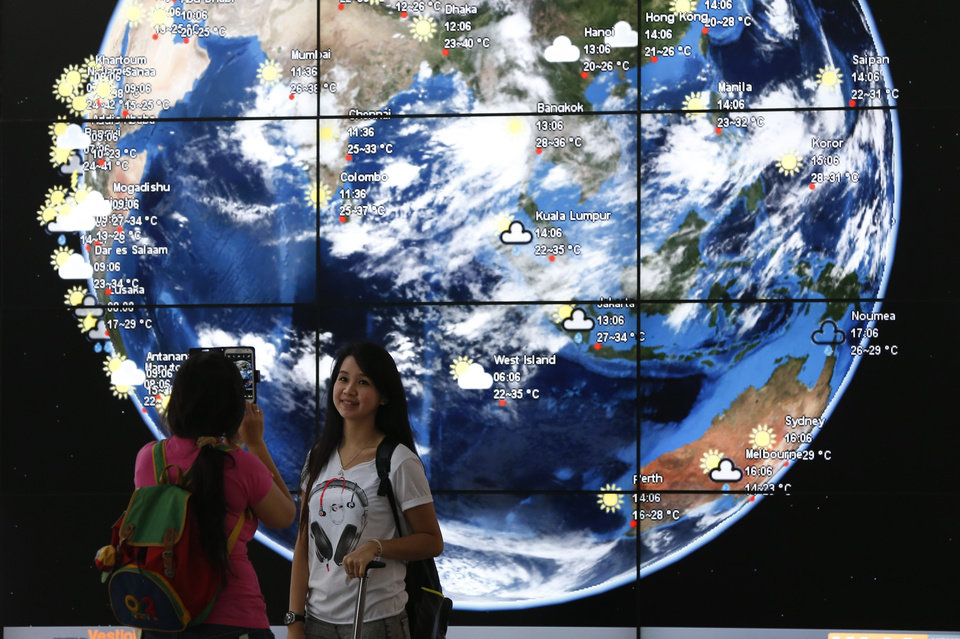 Photo - A Chinese girl is taken a picture in front of an electronic display showing the weather information of the cities in Asia at the Kuala Lumpur International Airport, in Sepang, Malaysia, Monday, March 17, 2014.  When someone at the controls calmly said the last words heard from the missing Malaysian jetliner, one of the Boeing 777's communications systems had already been disabled, adding to suspicions that one or both of the pilots were involved in the disappearance of the flight. (AP Photo/Vincent Thian)