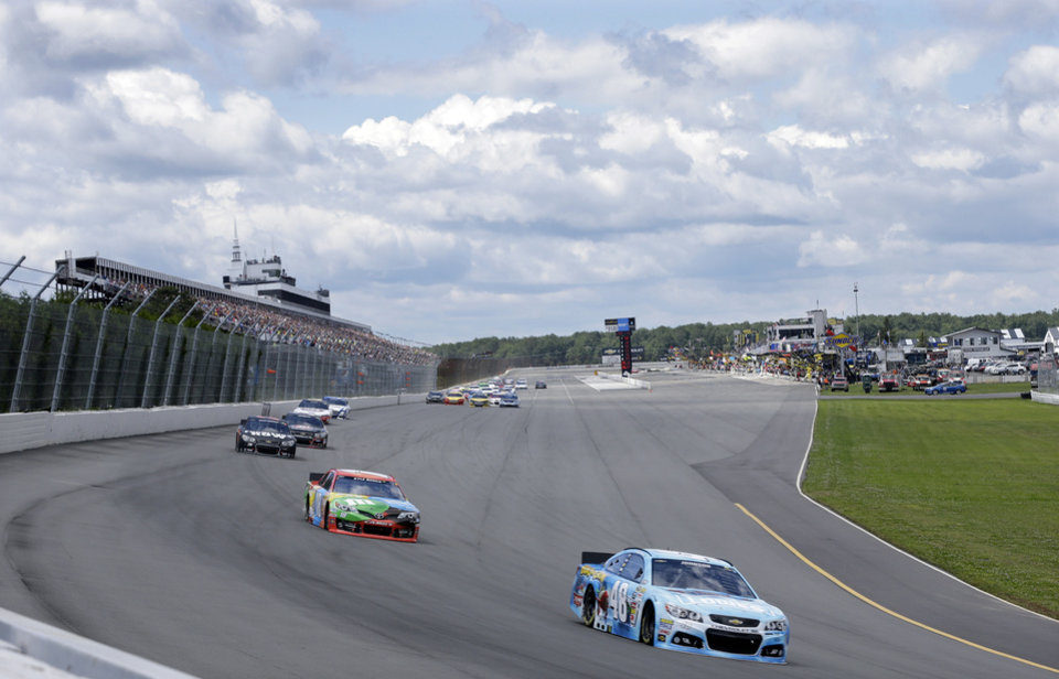 Photo - Driver Jimmie Johnson (48) leads Kyle Busch (18) in the early laps  of an NASCAR Sprint Cup Series auto race, Sunday Aug. 4, 2013, at Pocono Raceway in Long Pond, Pa. (AP Photo/Mel Evans)