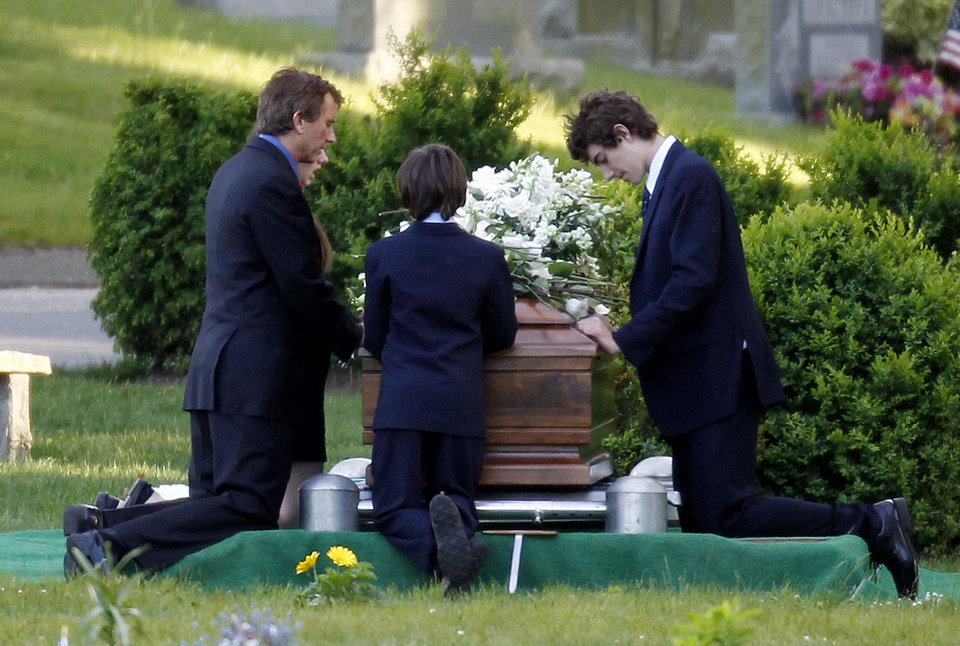 Photo -   Robert F. Kennedy Jr., left, kneels with his children at the casket of Mary Richardson Kennedy, in St. Francis Xavier Cemetery in Centerville, Mass., Saturday, May 19, 2012. Mary Richardson Kennedy was found dead of an apparent suicide last week at her home in Bedford, N.Y. (AP Photo/Michael Dwyer)