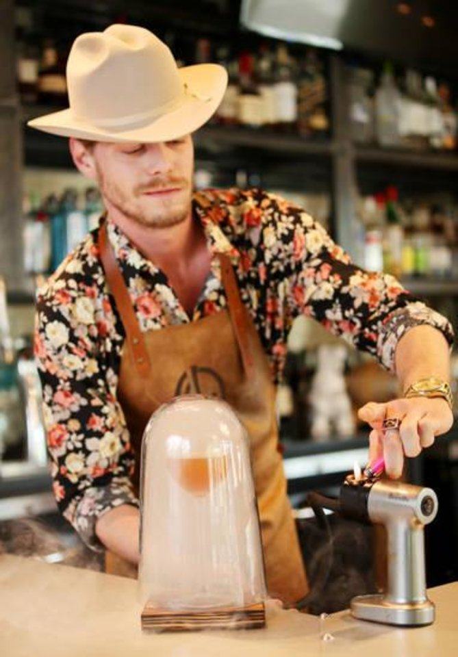 Photo - Jace Melton, bartender at Black Walnut, mixes up a CBD cocktail Wednesday, April 24, 2019. Photo by Doug Hoke