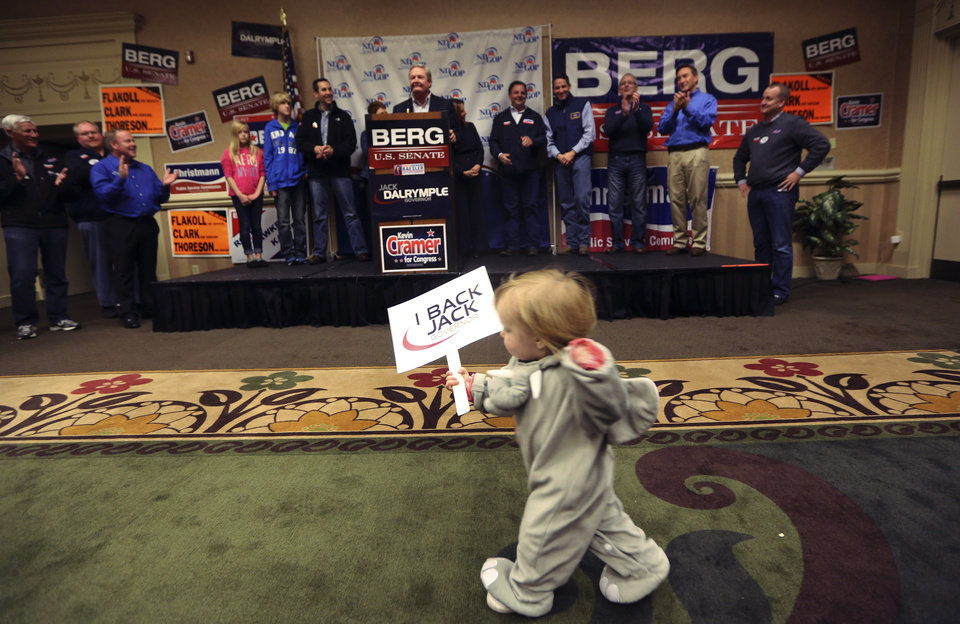 One-year-old Elsie Trandem caries a campaign sign as North Dakota Gov. Jack Dalrymple speaks before introducing Republican U.S. Senate candidate Rick Berg during a campaign stop in Fargo, N.D, Sunday, Nov. 4, 2012. Berg is running against Democrat Heidi Heitkamp for North Dakota's U.S Senate seat. (AP Photo/LM Otero)