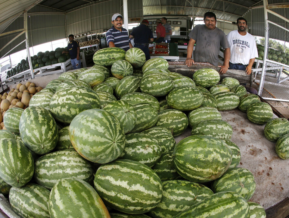 Workers stand beside a trailer of watermelons before they unload them at Joel Tumblson\'s produce stand on US 81. Watermelon farmers are busy preparing for the annual watermelon festival in Rush Springs on Aug. 10, 2013. Photo taken Wednesday, July 24, 2013. Photo by Jim Beckel, The Oklahoman.