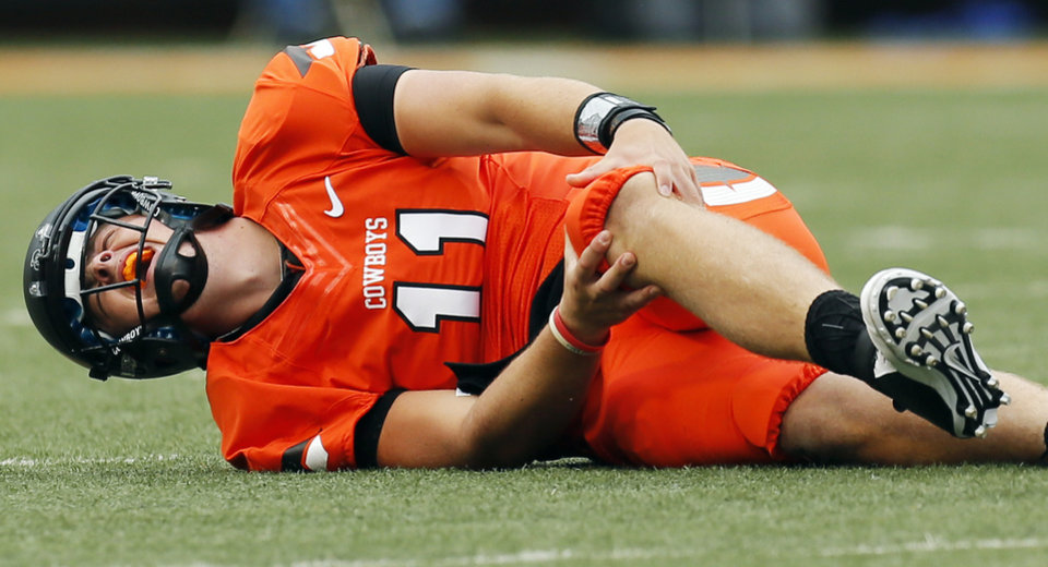 Photo - OSU quarterback Wes Lunt holds his knee after being injured on a play in the first quarter during a college football game between Oklahoma State University and the University of Louisiana-Lafayette (ULL) at Boone Pickens Stadium in Stillwater, Okla., on Sept. 15, 2012. Lunt left the game on crutches in the first quarter. Photo by Nate Billings, The Oklahoman