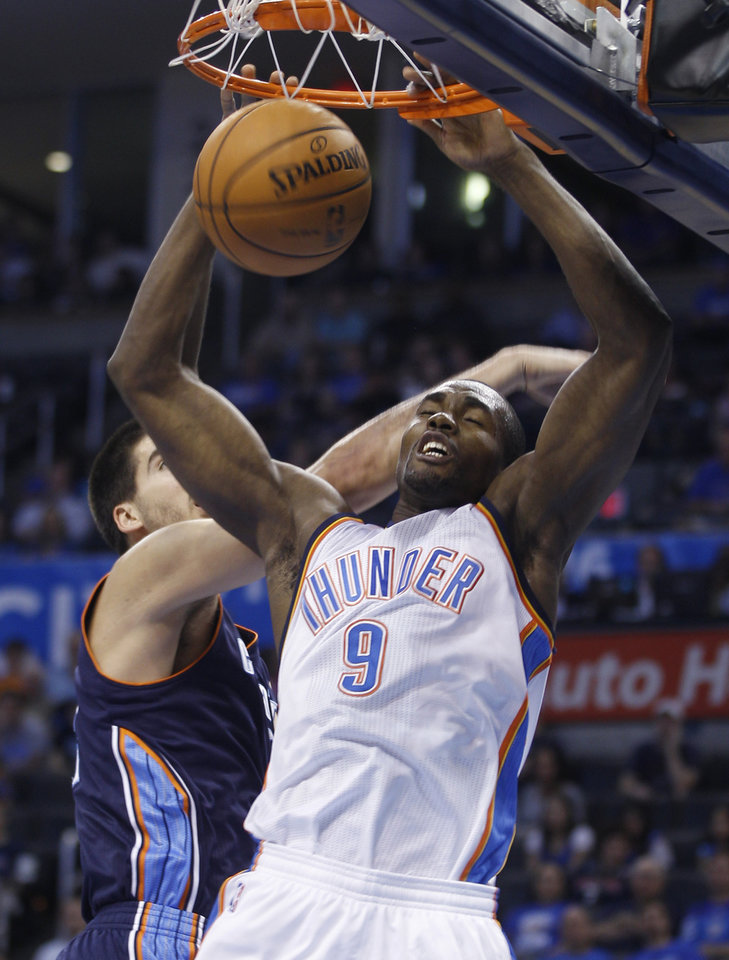 Photo -   Oklahoma City Thunder forward Serge Ibaka (9) dunks in front of Charlotte Bobcats forward Byron Mullens during the first quarter of a preseason NBA basketball game in Oklahoma City, Tuesday, Oct. 16, 2012. (AP Photo/Sue Ogrocki)