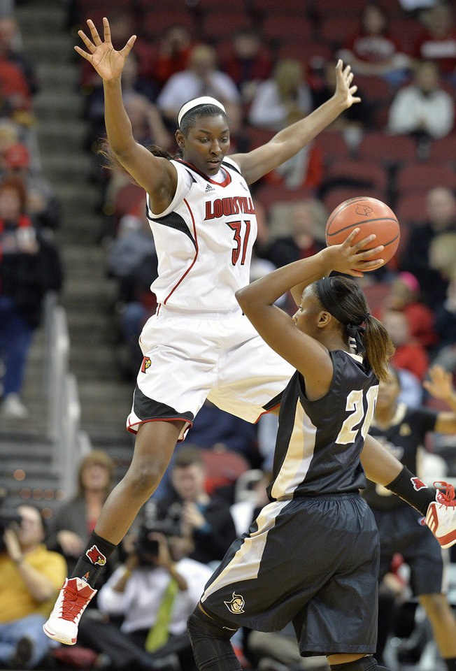 Photo - Louisville's Asia Taylor, left, attempts to block the passing lanes of Central Florida's Sara Djassi during the first half of an NCAA college basketball game on Wednesday, Jan. 15, 2014, in Louisville, Ky. (AP Photo/Timothy D. Easley)