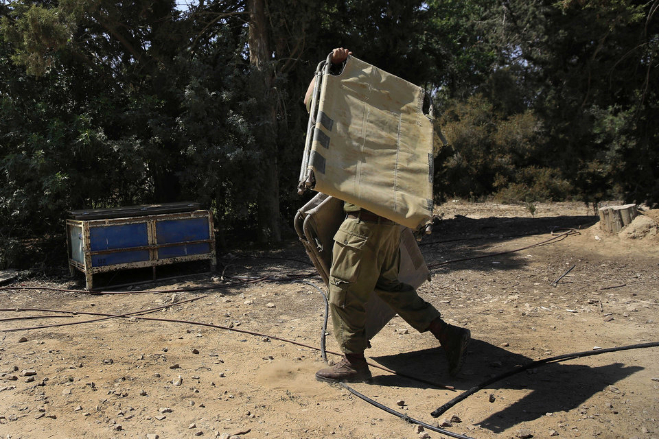 Photo - An Israeli soldier carries a bunk bed near the Israel Gaza border, Israel, Monday, July 7, 2014. The Islamic militant group Hamas that rules Gaza vowed revenge on Israel for the death of several of its members killed in an airstrike early Monday morning in the deadliest exchange of fire since the latest round of attacks began weeks ago. (AP Photo/Tsafrir Abayov)