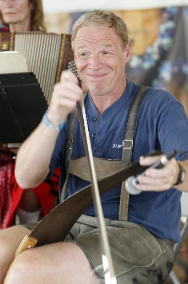 Photo -  Randy Adams with the band Alpenfest plays the singing saw during Oktoberfest in the Park in Choctaw, Monday, September 3, 2012. Photo By David McDaniel/The Oklahoman Archives