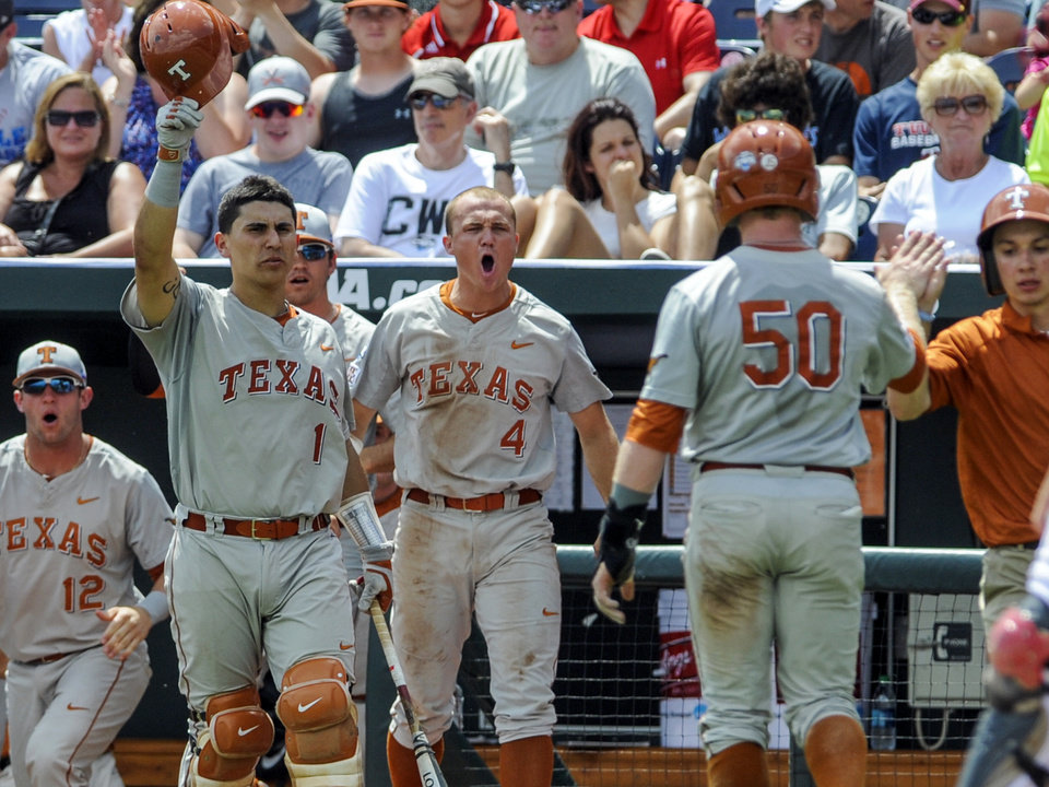 Photo - Texas' Zane Gurwitz (50) is greeted at the dugout by teammates Tres Barrera (1), Collin Shaw (4) and Jacob Felts (12) after he scored a run on a sacrifice fly by Ben Johnson in the third inning of an NCAA baseball College World Series elimination game in Omaha, Neb., Monday, June 16, 2014. (AP Photo/Eric Francis)