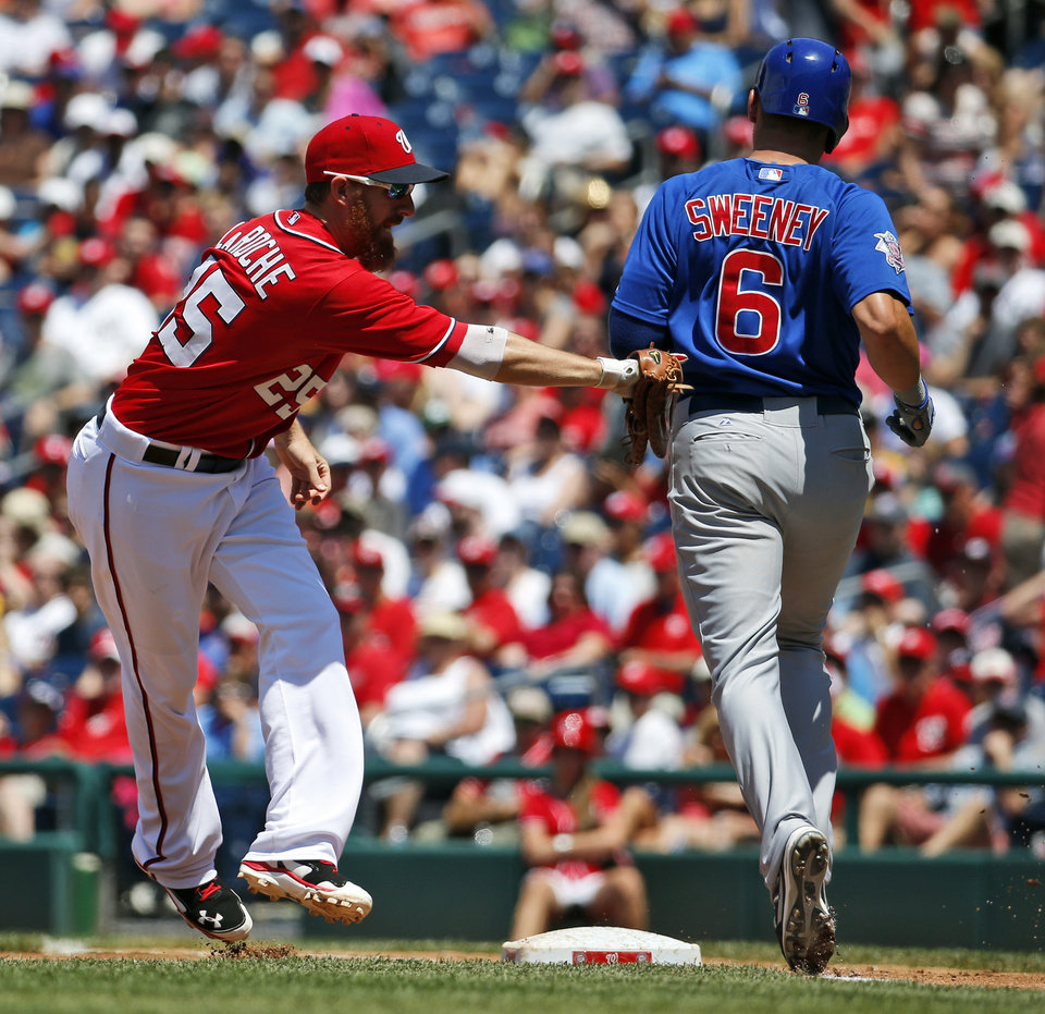 Washington Nationals first baseman Adam LaRoche, left, tags Chicago Cubs\' Ryan Sweeney, right, out at first base during the third inning of a baseball game at Nationals Park, Sunday, July 6, 2014, in Washington. Sweeny was called safe, but the play was overturned and he ruled out. (AP Photo/Alex Brandon)