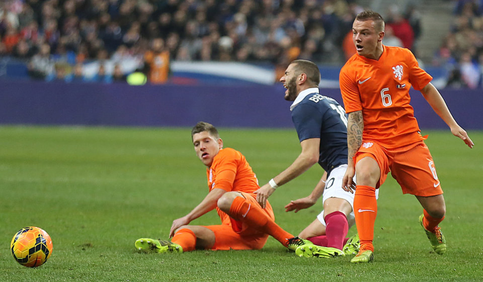 Photo - Netherlands' Jordy Clasie, right, vies for the ball with France's Karim Benzema, center, during the friendly soccer match between France and Netherlands at the Stade de France, in Saint Denis, north of Paris, Wednesday March 5, 2014.(AP Photo/Remy de la Mauviniere)