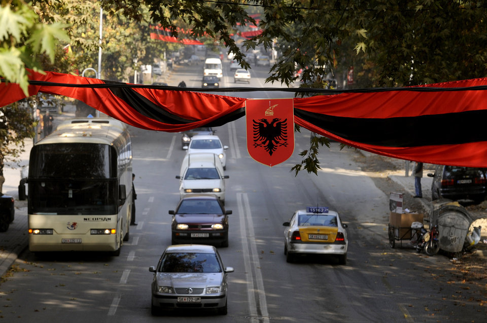 Photo -   Red and black flags with Albanian coat of arms hang over a street in Macedonia's capital Skopje, on Saturday, Nov.24, 2012. Macedonian capital Skopje, particularly the parts populated with ethnic Albanians, are flooded with Albanian flags, in the eve of the celebration of 100 years of Albania's independence and the national flag. Ethnic Albanians make up a quarter of Macedonia's 2.1 million people and are the largest ethnic minority in the country. (AP Photo/Boris Grdanoski)