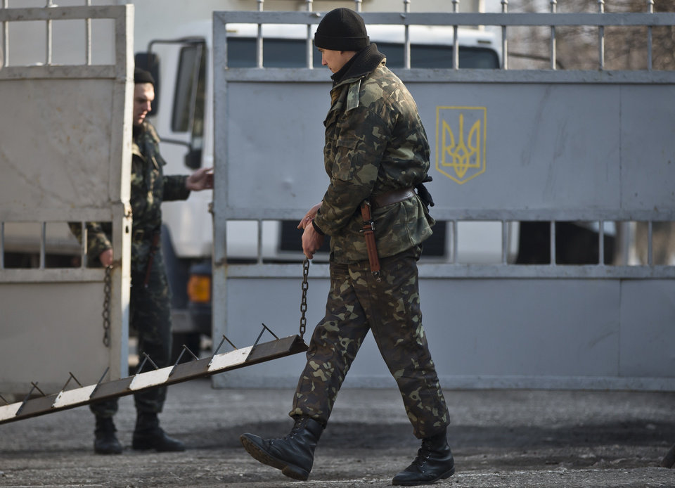 Photo - An Ukrainian soldier removes a tyre piercing road block at the gate of the Ukrainian infantry base in Perevalne, Ukraine, Wednesday, March 12, 2014. The Group of 7 world leaders said in a statement released from the White House on Wednesday that they won't recognize results of a referendum for the Crimea region to split from Ukraine and join Russia.(AP Photo/Vadim Ghirda)