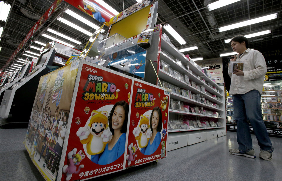 Photo - A shopper looks at Nintendo 3DS games at an electronics store in Tokyo, Wednesday, May 7, 2014.Nintendo Co. sank to a loss for the fiscal year ended March as sales of its Wii U game machine continued to lag, but the Japanese manufacturer of Pokemon and Super Mario games promised Wednesday to return to profit this year. (AP Photo/Shizuo Kambayashi)