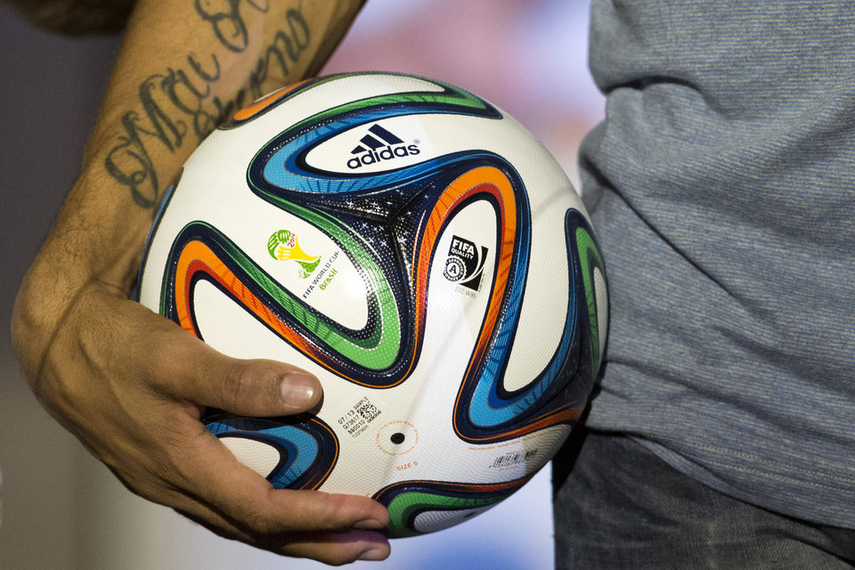 Photo - FILE - In this Dec. 3, 2013 file photo, Brazilian soccer player Hernanes holds the 2014 World Cup official soccer ball, called Brazuca, after it was unveiled in Rio de Janeiro, Brazil. The competition on the pitch in has yet to start, but the fight over World Cup consumers is already intense _ and no more so than between the athletic companies that are jockeying for their once-every-four-years shot at the ever-growing soccer market. (AP Photo/Victor R. Caivano, File)
