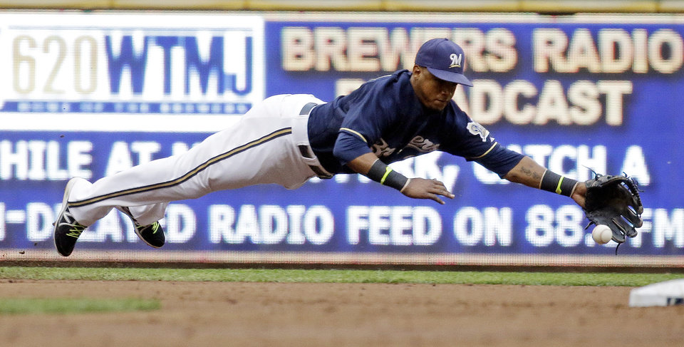 Photo - Milwaukee Brewers shortstop Jean Segura makes a diving try at a single hit by Colorado Rockies' Michael McKenry during the third inning of a baseball game Friday, June 27, 2014, in Milwaukee. (AP Photo/Morry Gash)