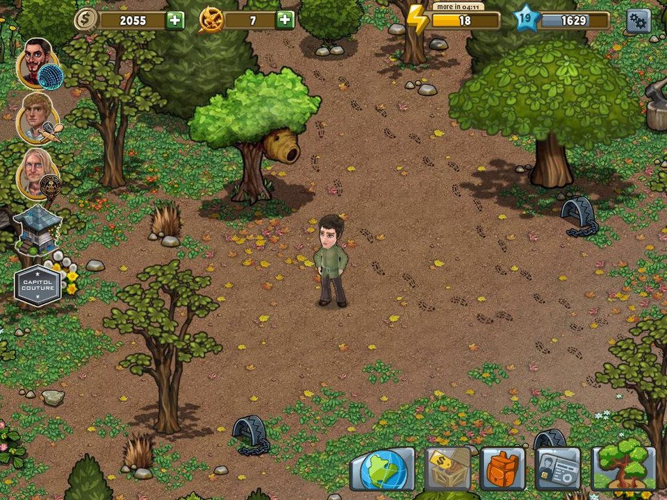 "A tracker jacker nest in the woods, shown hanging from a tree near the back of this screen shot, is the scene of some of the action in ""The Hunger Games Adventures"" mobile application for the iPad. <strong></strong>"