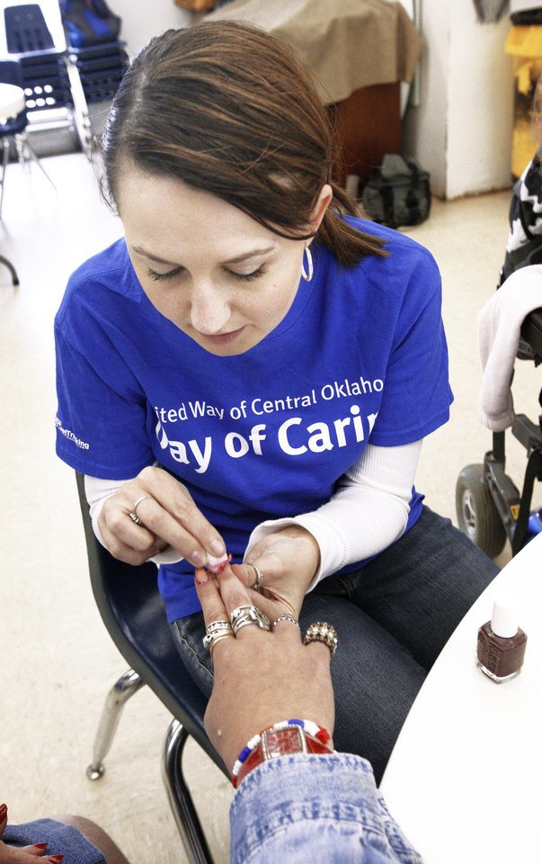 Photo - Left: Volunteer Erika Huffman, from Newcastle, worked on a client's nails at the Oklahoma Foundation for the Disabled during United Way of Central Oklahoma's annual Day of Caring event on Friday.  Photos by Paul B. Southerland, The Oklahoman