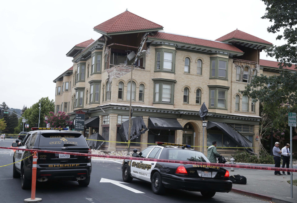 Photo - Police cars block the street outside a heavily damaged building following an earthquake Sunday, Aug. 24, 2014, in Napa, Calif. A large earthquake caused significant damage in California's northern Bay Area early Sunday, sending at least 70 people to a hospital, igniting fires, knocking out power to tens of thousands and sending residents running out of their homes in the darkness. (AP Photo/Eric Risberg)