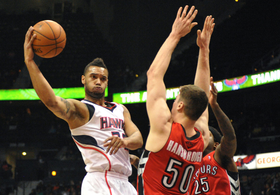 Photo - Atlanta Hawks' Mike Scott, left, passes around Toronto Raptors' Tyler Hansbrough (50) and John Salmons (25) in the first half of their NBA basketball game Tuesday, March 18, 2014, in Atlanta. (AP Photo/David Tulis)