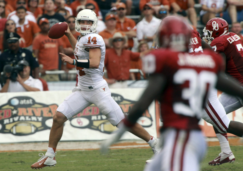 Photo -   Texas quarterback David Ash (14) looks to pass as Oklahoma defenders close in during the first half of an NCAA college football game at the Cotton Bowl Saturday, Oct. 13, 2012, in Dallas. (AP Photo/Michael Mulvey)