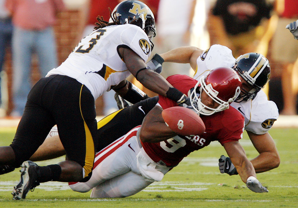 Photo - Oklahoma's Juaquin Iglesias (9) fumbles the ball while being brought down by Missouri's Cornelius Brown (13) and Stryker Saulak (38) during the first half of the college football game between  the University of Oklahoma Sooners (OU) and the University of Missouri Tigers (MU) at the Gaylord Family Oklahoma Memorial Stadium on Saturday, Oct. 13, 2007, in Norman, Okla.By CHRIS LANDSBERGER, The Oklahoman