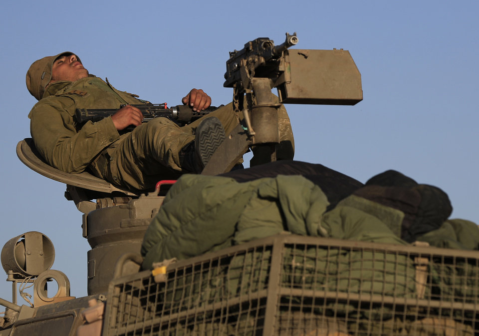 Photo - An Israeli soldier rests on a mobile artillery unit at a position on the Israel-Gaza border, Friday, July 11, 2014. Gaza rocket fire struck a gas station and set it ablaze Friday in southern Israel, seriously wounding one person as rocket fire also came from Lebanon for the first time in the four-day-long offensive. Rocket fire by Palestinian militants continued from Gaza toward various locations in southern Israel. (AP Photo/Tsafrir Abayov)