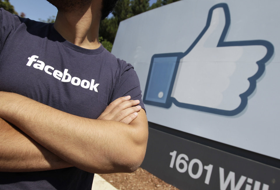 Photo -   A Facebook worker waits for friends to arrive outside of Facebook headquarters in Menlo Park, Calif., Friday, Aug. 17, 2012. Facebook stock is trading at $19 and has lost half its market value since its May public offering. (AP Photo/Paul Sakuma)