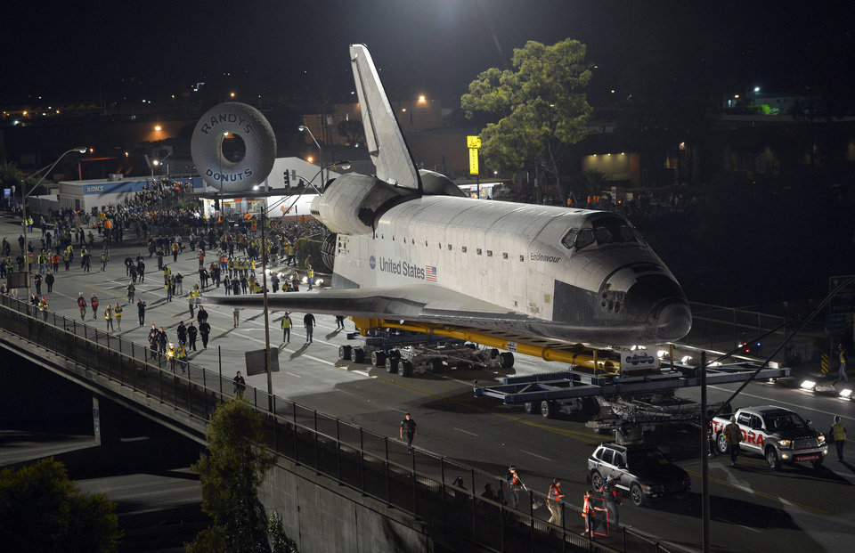 The Space Shuttle Endeavour is slowly moved across Interstate 405 by a Toyota Tundra, Friday, Oct.12, 2012, in Los Angeles. The shuttle is on its last mission � a 12-mile creep through city streets. It will move past an eclectic mix of strip malls, mom-and-pop shops, tidy lawns and faded apartment buildings. Its final destination: California Science Center in South Los Angeles where it will be put on display. (AP Photo/Mark J. Terrill)