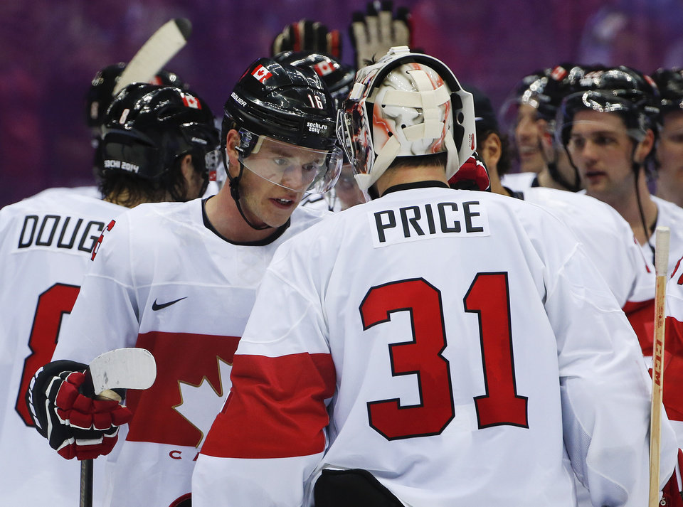 Photo - Canada forward Jonathan Toews congratulates Canada goaltender Carey Price after Canada's 2-1 win over Latvia during a men's quarterfinal ice hockey game at the 2014 Winter Olympics, Wednesday, Feb. 19, 2014, in Sochi, Russia. (AP Photo/Julio Cortez)