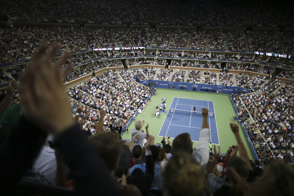 Photo - Spectators cheer during a quarterfinal between Roger Federer, of Switzerland, and Gael Monfils, of France, at the U.S. Open tennis tournament, Thursday, Sept. 4, 2014, in New York. (AP Photo/John Minchillo)